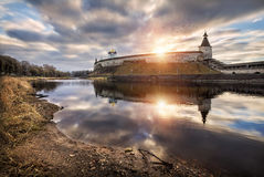 Winter does not look like winter. View of the Pskov fortress with reflection in the river and the autumn-winter landscape Stock Image