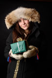 Winter dressed young girl with a Christmas gift royalty free stock image