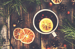 Winter drink with lemon, cranberries and spices on wooden background Stock Photo