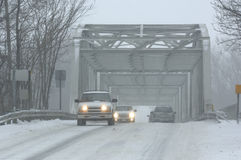 Winter Driving. Vehicles crossing a bridge during a blizzard Royalty Free Stock Photography