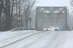 Winter Driving. Vehicles crossing a bridge during a blizzard Stock Image