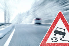 Winter Driving - Icy Road with Warning Sign Royalty Free Stock Images