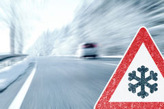 Winter Driving - Icy Road with Warning Sign Stock Images