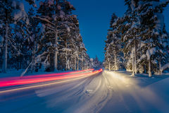 Winter Driving - Lights of car and winter road in forest at nigh Stock Photos