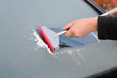 Winter driving - scraping ice from a windshield Royalty Free Stock Photo