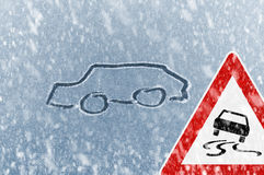 Winter Driving - Snow on an ice covered windshield with sketched car and warning sign Stock Photo