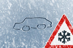 Winter Driving - Snow on an ice covered windshield with sketched car and warning sign Royalty Free Stock Photos