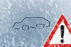 Winter Driving - Snow on an ice covered windshield with sketched car and warning sign Stock Image