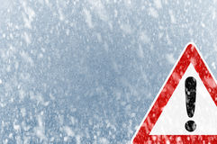 Winter Driving - Snow on an ice covered windshield with warning sign Royalty Free Stock Images