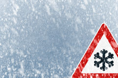 Winter Driving - Snow on an ice covered windshield with warning sign Stock Photos