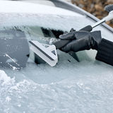 Winter Driving - Woman Scraping Ice from a Windshield Royalty Free Stock Images