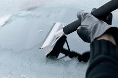 Winter Driving - Woman Scraping Ice from a Windshield Stock Images