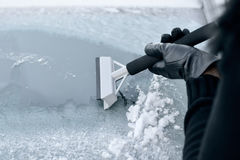 Winter Driving - Woman Scraping Ice from a Windshield Stock Photos