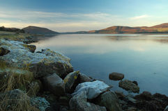Winter Dusk, Loch Fleet. Calm cold waters of Loch Fleet at dusk, with frosted rocks on the shore, in winter, North of Scotland Stock Images