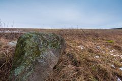 Winter or early spring landscape of boulder stones on fields Royalty Free Stock Image
