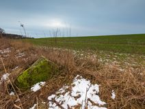 Winter or early spring landscape of boulder stones on fields Royalty Free Stock Photo