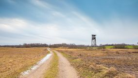 Winter or early spring landscape of field with raised hide Royalty Free Stock Image