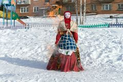 The effigy of the Shrovetide in Russian folk costume is burned in the snow during a traditional national holiday of Seeing off. Winter. The effigy of the stock images