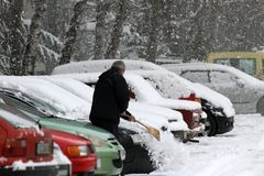 Winter Ein Mann mit einem Besen säubert Auto vom Schnee auf der Straße nach großem Schneesturm in der Stadt, alle Autos unter Sch Lizenzfreies Stockbild