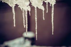 Winter-Eiszapfen, die unten vom Dach hängen Lizenzfreie Stockfotografie