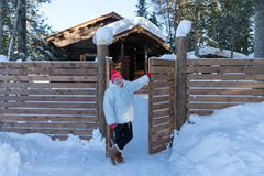 Elderly woman stands and smiles happily near the gate near a wooden house among the snowdrifts in the forest royalty free stock photography
