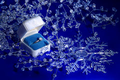 Winter Engagement. A diamond ring in snow and ice decoration on a blue background Royalty Free Stock Photos