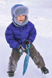 Winter enjoyment. Lively happy kid playing outside holding sledge, wintertime Royalty Free Stock Photography