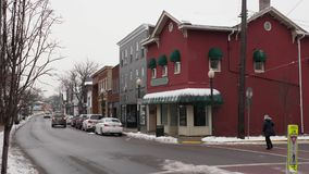Winter establishing shot of generic small town main street storefronts. A daytime winter exterior establishing shot of a generic small town's Main Street stock footage