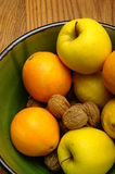 Winter european fruits in a bowl. Some french winter fruits, apple, orange, nuts, lemon in a green bowl on wooden table Royalty Free Stock Photo