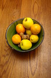 Winter european fruits in a bowl. Some french winter fruits, apple, orange, nuts, lemon in a green bowl on wooden table Royalty Free Stock Images
