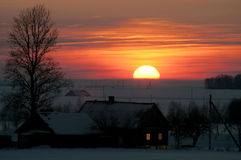 Winter evening. Rural house in the winter evening in beams of the coming sun Stock Photos