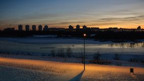 Winter evening cityscape. view of the residential area across the river in the background of the sunset. Winter evening cityscape. beautiful view from the coast stock photo