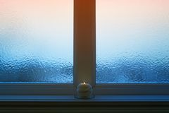 Frosted evening window with a candle burning. Winter evening. Frosted window, and ball of yarn decorative candle burning Stock Images