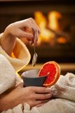 Winter evening with hot tea. Winter evening with hot blood orange tea, young woman in bathrobe holding mug and spoon in front of fireplace Royalty Free Stock Images