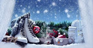 Winter evening with hot tea and christmas decoration on the wind. Winter snowy evening with cup of hot tea,old figure skates and vintage style lantern and Royalty Free Stock Photos