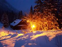 Winter evening landscape. Wooden house covered with snow clarified street electric lantern. Wintering in the mountains and in the royalty free stock photo