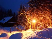 Winter evening landscape. Wooden house covered with snow clarified street electric lantern. Wintering in the mountains and in the royalty free stock photography