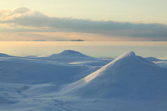 Winter evening on the sea. Snow hills on the seashore, sunset time Royalty Free Stock Images