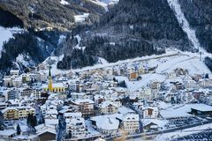 Winter evening in ski resort Ischgl in Tyrol Alps. Snow covered town is located among mountains and it`s getting dark very early. Ischgl, Austria - December 29 stock images
