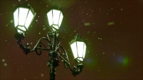 Winter evening. Snow flies past a street lamp in the old style. Defocused. stock video footage