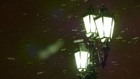 Winter evening. Snow flies past a street lamp in the old style. Defocused.