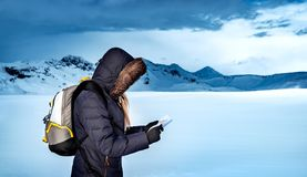 Winter expedition to Iceland. Traveler girl with a map in the snowy area of the North Pole, extreme winter travel to the mountains, active lifestyle of a young stock image