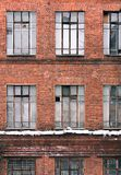 Winter facade of an old brick building in loft style. High Windows and textural materials. Architectural background Stock Images