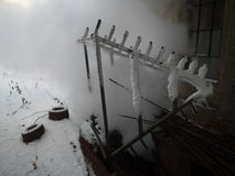 Winter factory steam. Metal construction and two car tires stock image