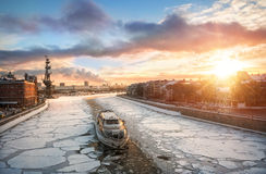 Winter fairway. Pleasure boat floating in the winter Moscow River through the ice floes and the setting sun over the city Stock Photos