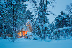 Winter fairy night - wooden cottage in snowy forest Stock Image