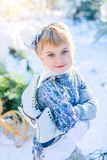 Winter fairy tale. Beautiful little girl is walking in a snowy forest royalty free stock photography