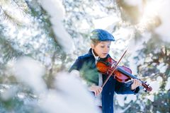 Winter fairy tale. Cute boy violinist in winter forest. royalty free stock photos