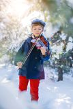 Winter fairy tale. Cute boy violinist in winter forest. royalty free stock photography
