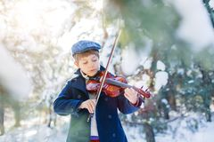Winter fairy tale. Cute boy violinist in winter forest. stock image